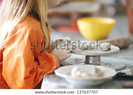 clay potter hands wheel pottery work workshop teacher and girl pupil - stock photo