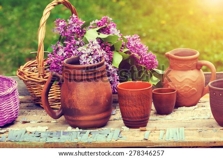 Clay utensil on retro wooden table in the garden - stock photo