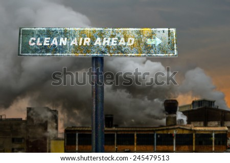 Clean air ahead slogan on the road sign in front of the polluting factory. - stock photo