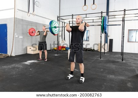 Clean and jerk workout at fitness gym center - stock photo