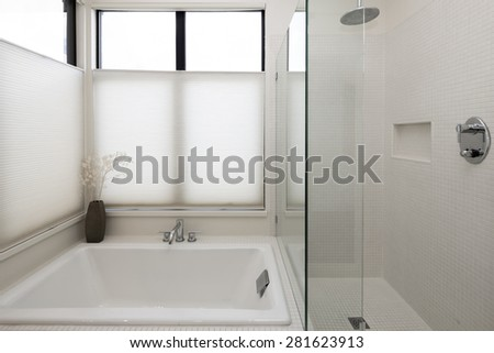 Clean contemporary bathroom with glass shower and bath tub.  - stock photo