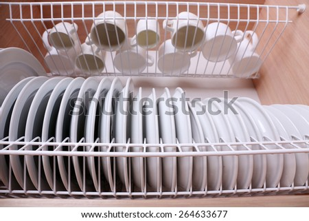 Clean dishes drying on metal dish rack on shelf - stock photo