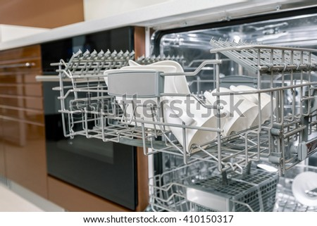 Clean dishes in open dishwasher machine - stock photo