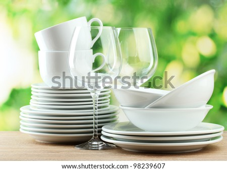 Clean dishes on wooden table on green background - stock photo