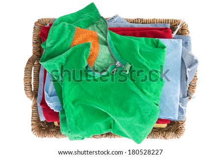 Clean fresh washed summer clothes in a basket neatly folded and viewed from above with a colorful green shirt on top of the pile, overhead close up view isolated on white - stock photo
