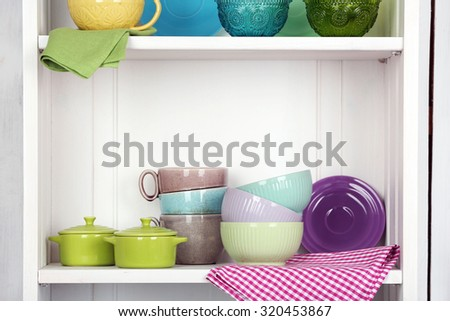 Clean glasses, plates and cutlery on shelf in kitchen cupboard - stock photo