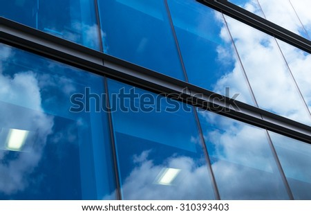 Clean modern style office building with reflected blue sky in the windows - stock photo