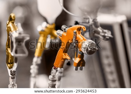 Clean paint gun in the workshop closeup photo - stock photo