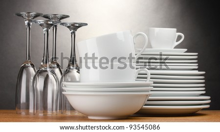 Clean plates, glasses and cups on wooden table on grey background - stock photo