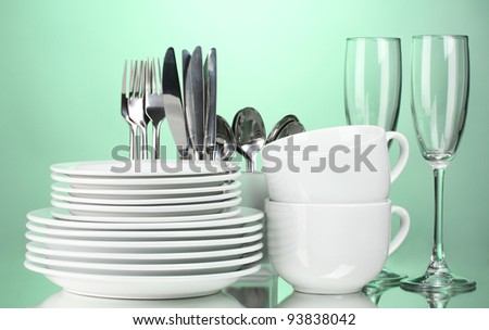 Clean plates, glasses, cups and cutlery on green background - stock photo