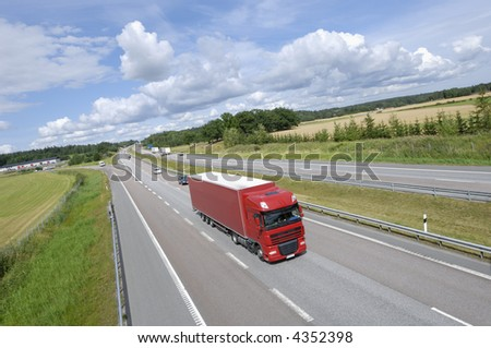 clean red truck on highway surrounded by country-side and in extreme wide-angle - stock photo