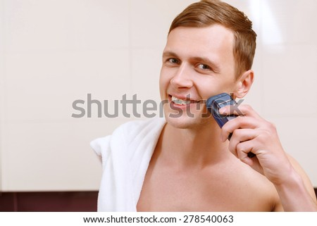 Clean shave. Smiling young handsome man shaving with help of electric razor in front of mirror n bathroom. - stock photo