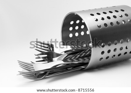 Clean shiny cutlery and aluminum stand over white background. - stock photo