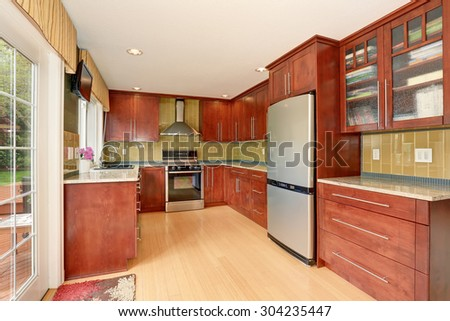 Clean style kitchen with stained wood cabinets, and nice counter tops. - stock photo