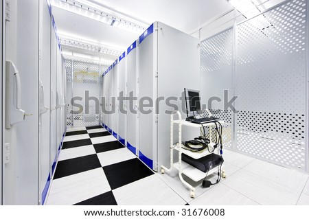 Clean suite in a data center with the perforated doors of server racks and a computer cart - stock photo