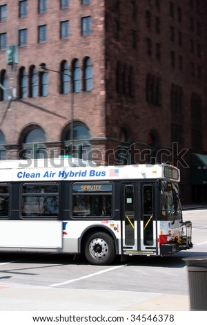 Clean-technology hybrid bus in a city center.  Panning shot. - stock photo