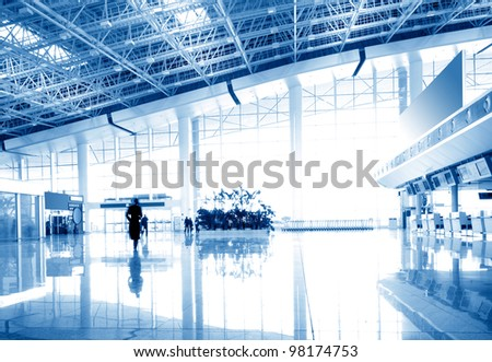 Clean tiled floor, reflection of light on floor and blurred view of people walking - stock photo
