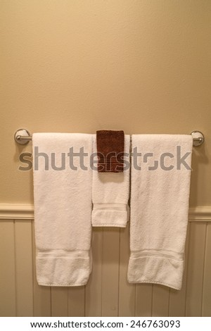 Clean towels in a hotel bathroom hanging on a chrome towel rack - stock photo