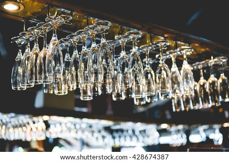 Clean washed and polished glasses hanging over a bar rack. - stock photo