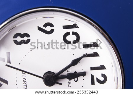 Clean white clock showing five seconds to midnight - stock photo