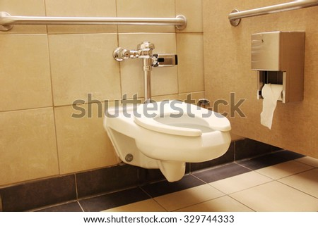 Clean white porcelain toilet with rails for handicap - stock photo