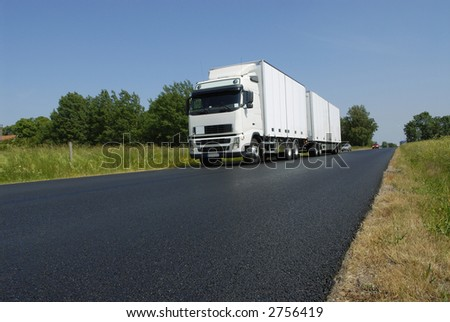clean white truck driving, surrounded by countryside - stock photo