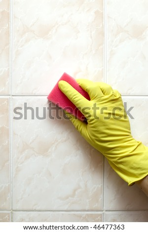Cleaner is cleaning tiles in bathroom with red sponge - stock photo