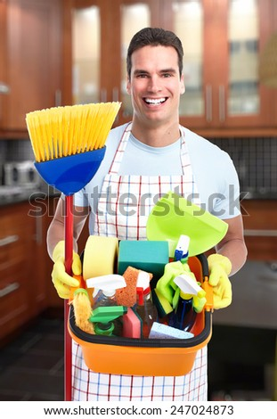 cleaner man with a broom in modern house. - stock photo