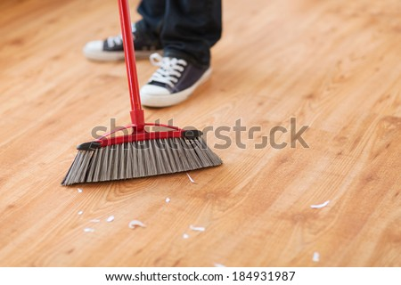 cleaning and home concept - close up of male brooming wooden floor - stock photo