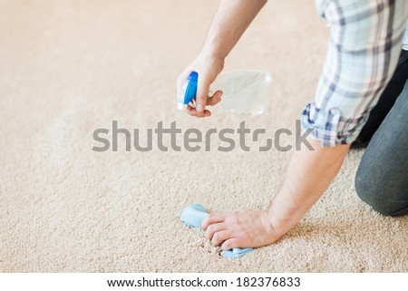 cleaning and home concept - close up of male cleaning stain on carpet with cloth - stock photo