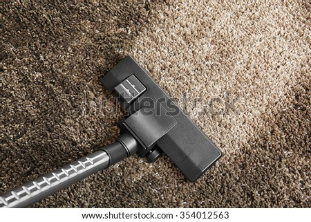 Cleaning concept - vacuum cleaner on grey soft carpet, close up - stock photo