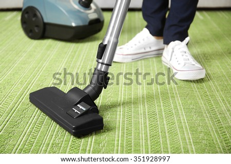 Cleaning concept - woman cleaning the room with carpet sweeper, close up - stock photo