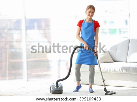 Cleaning concept. Young woman cleaning carpet with vacuum cleaner - stock photo