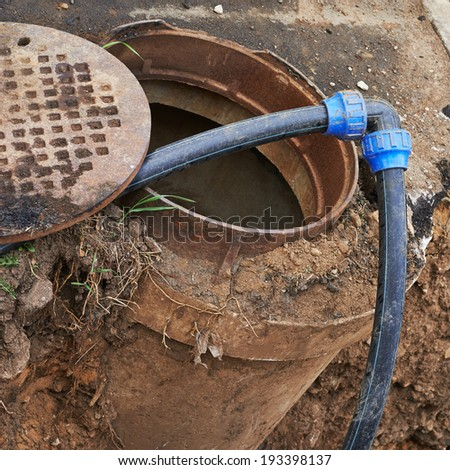Cleaning equipment tubes in a sewer manhole composition - stock photo