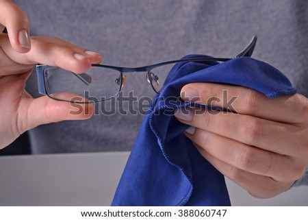 Cleaning eye glasses. - stock photo