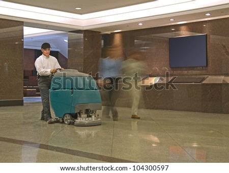 Cleaning floor in office building lobby - stock photo