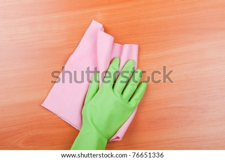 Cleaning furniture table in green glove with pink sponge - stock photo