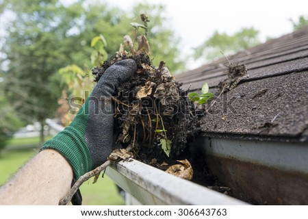 Cleaning gutters during the summer time.  - stock photo