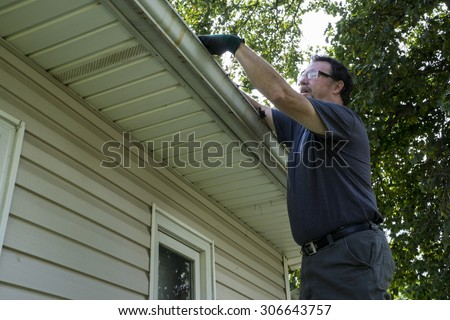 Cleaning gutters on a residential home. - stock photo