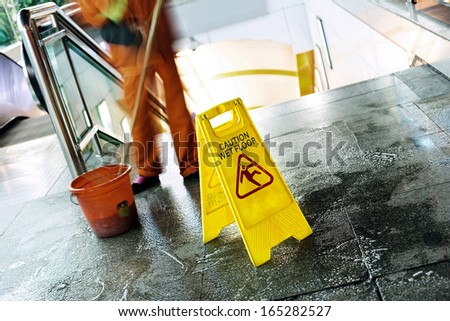 cleaning in progress, and wet floor caution sign besides.  - stock photo