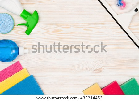 Cleaning items and tools lying on textured white floor background. Frame for cleaning concept or advertising. Empty copy space around products. - stock photo
