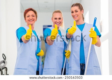 Cleaning ladies working in team showing the thumbs up sign - stock photo