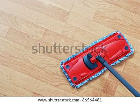 Cleaning laminate. Red mop on hardwood floors. - stock photo