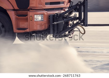 Cleaning machine washes the city street early in the morning. - stock photo