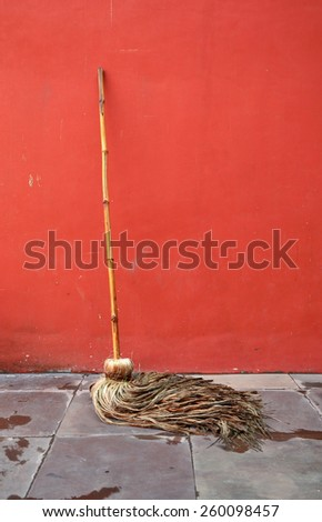 Cleaning mop lean against red wall - stock photo
