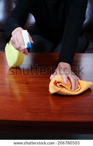 Cleaning or polishing timber furniture. - stock photo