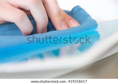 Cleaning  screen on modern digital tablet pc. - stock photo