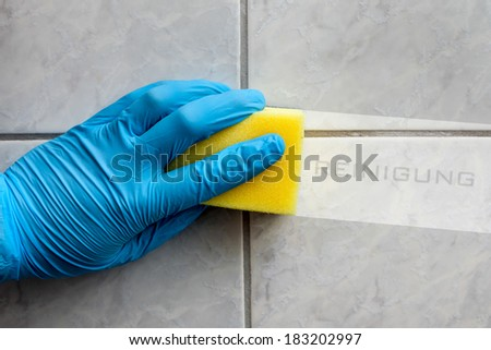 Cleaning sponge held in hand while cleaning bathroom with german lettering reinigung (cleaning in english translation) - stock photo