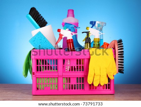 Cleaning supplies in basket on blue background - stock photo