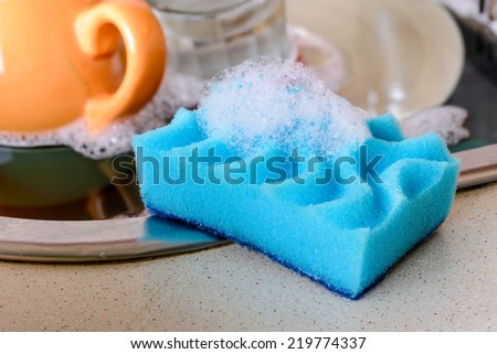 Cleaning the dirty dishes with a blue sponge with detergent in a sink - stock photo